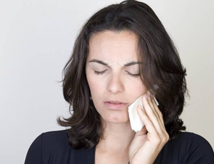 Woman holding cold compress to cheek